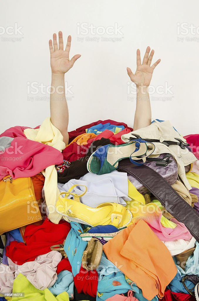 Man buried under an untidy cluttered woman wardrobe. stock photo