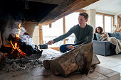 Man burning logs in the fireplace while relaxing with his partner at a winter lodge