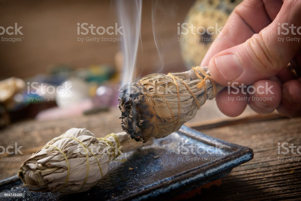 Man burning white sage incense stock photo