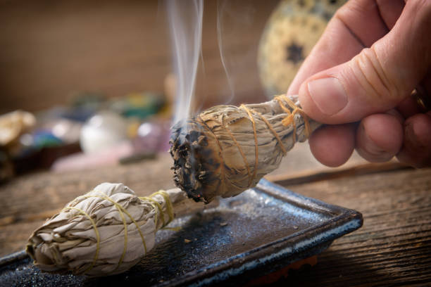 Man burning white sage incense stock photo