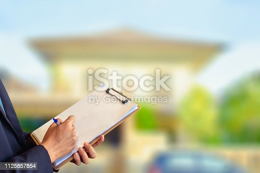 Man business salesman Sell house with computer On house and tree blurry background.For home business contracting or agreement and home warranty image