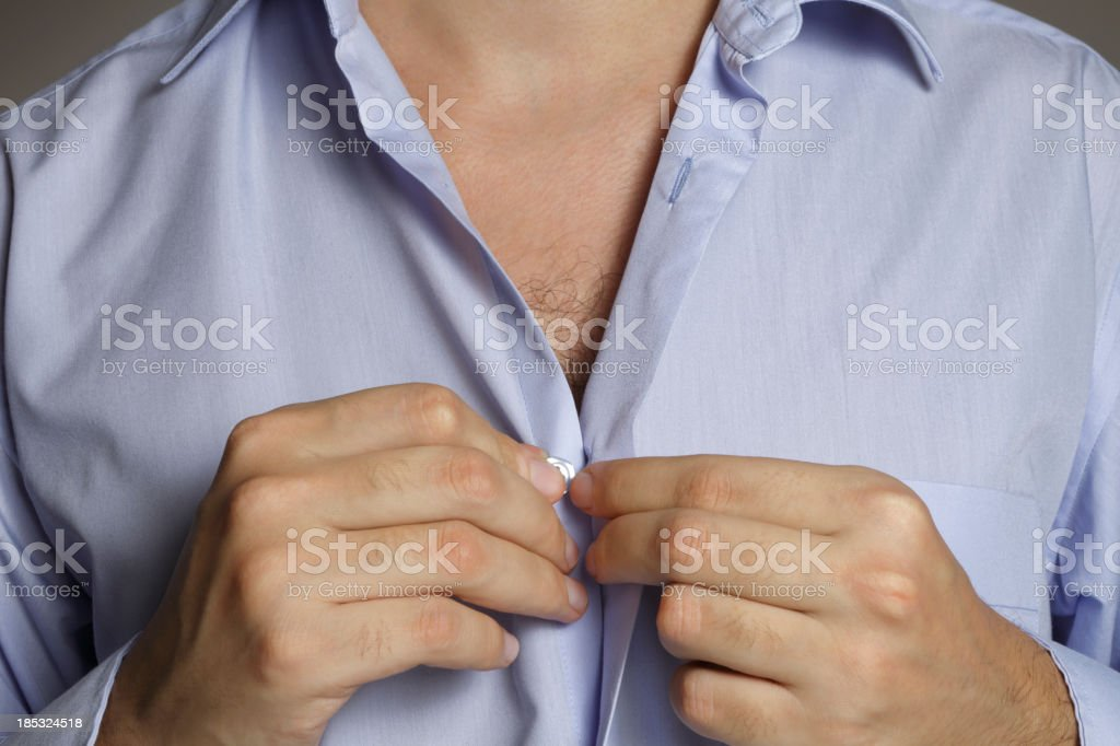 A man buttoning a blue shirt with a gray background stock photo