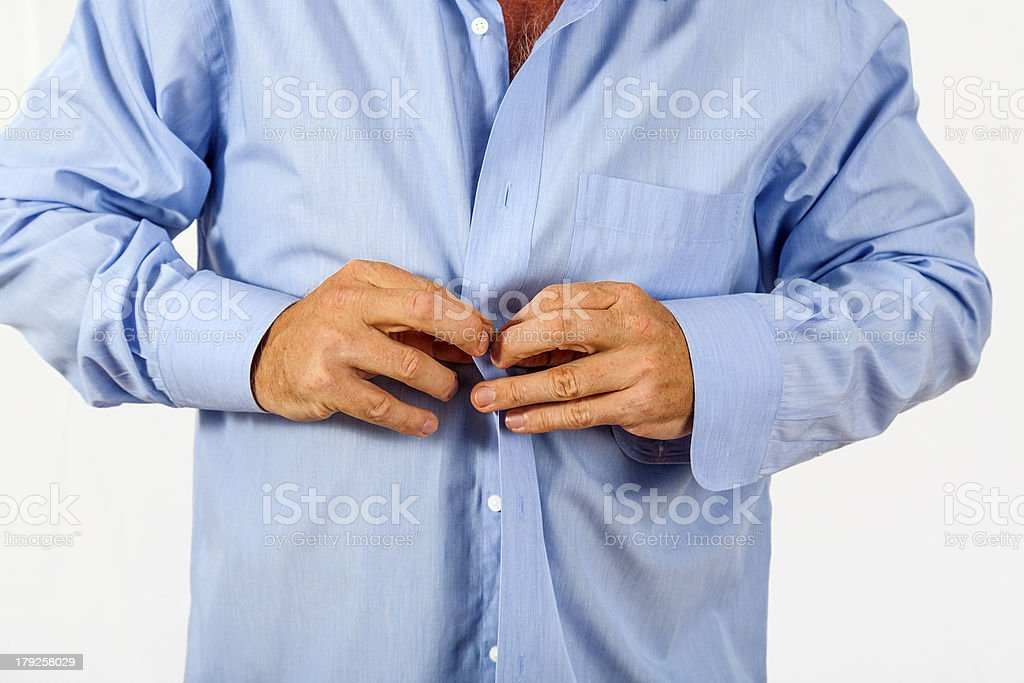 man buttoning his shirt stock photo