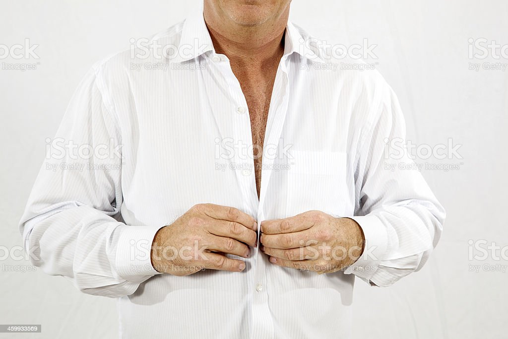 man buttoning his white office shirt in the morning stock photo