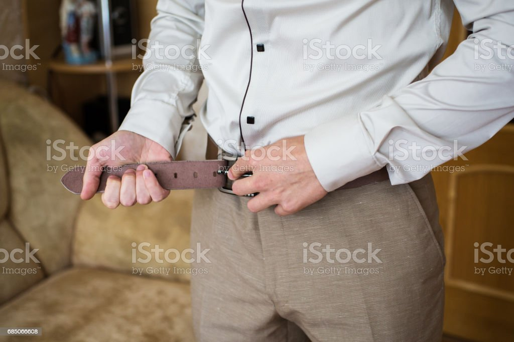 Man buttons belt. Men's style. Professions. To prepare for work, royalty-free stock photo