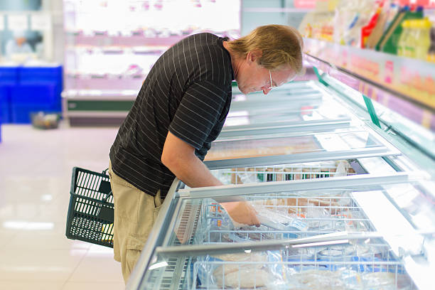 man buy frozen fish in the supermarket stock photo