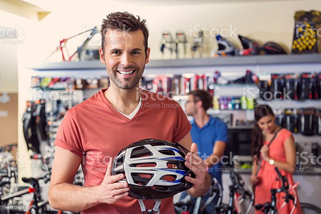 Man buying a helmet Bike store: man holding a bicycle helmet and smiling at camera with two people in the background. Adult Stock Photo