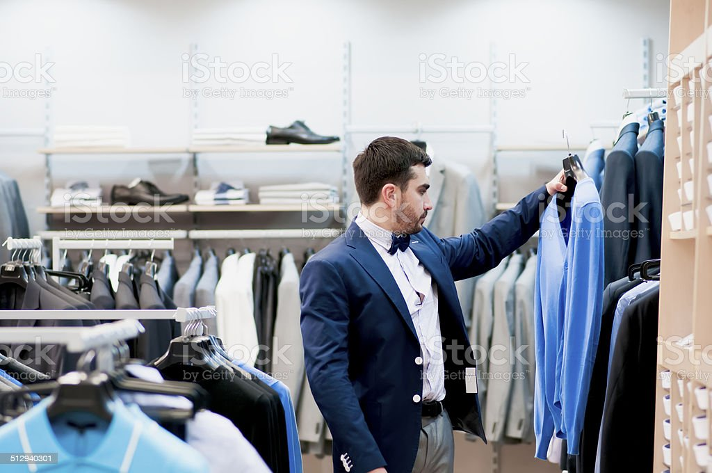 Man buying a tee-shirt at a boutique. stock photo
