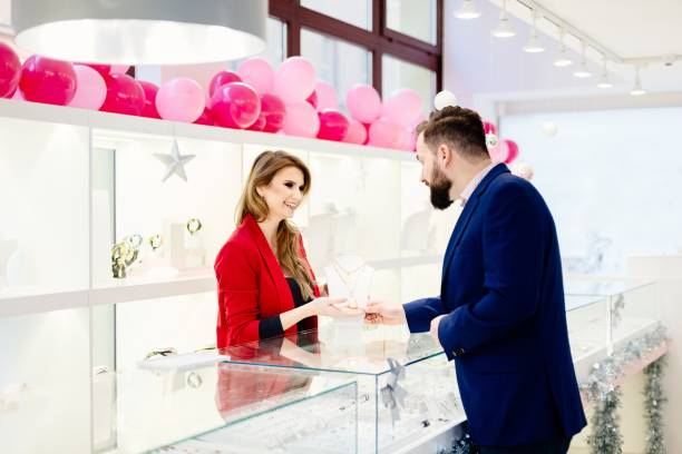 man kauft eine valentines geschenk bei einem juwelier - diamanten kaufen stock-fotos und bilder