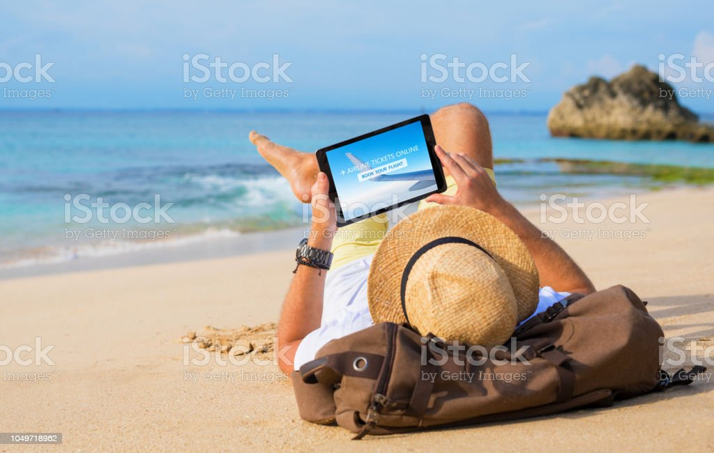 Man buying airline tickets online on tablet while relaxing on beach. stock photo