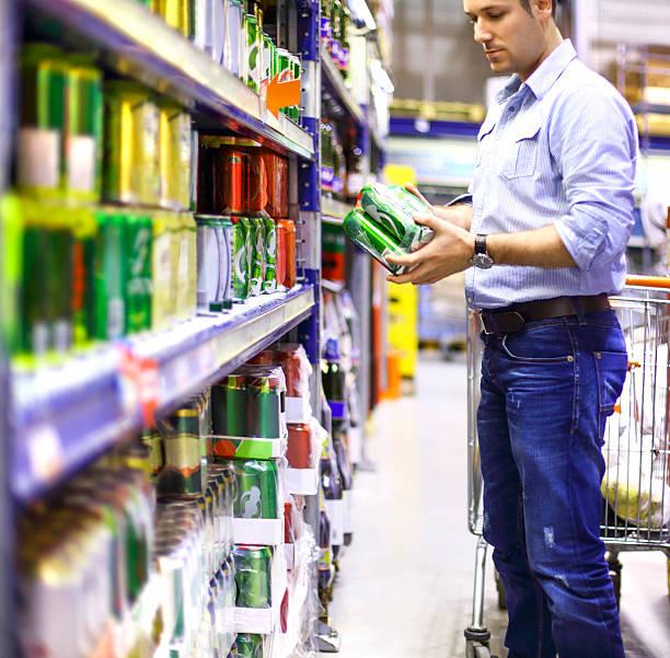 homme acheter de la bière dans un supermarché. - pack de six photos et images de collection