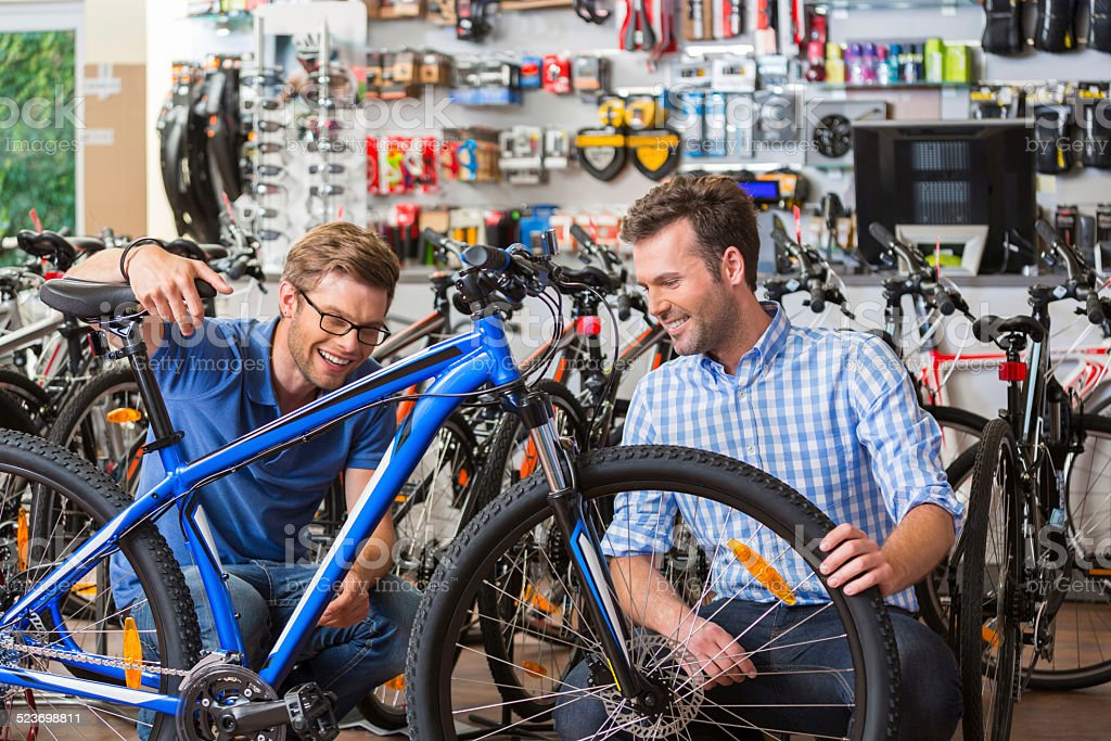 Man buying bicycle in sport store Man buying a bicycle in bike store, talking with shop assistant and watching the mountain bike together. Adult Stock Photo