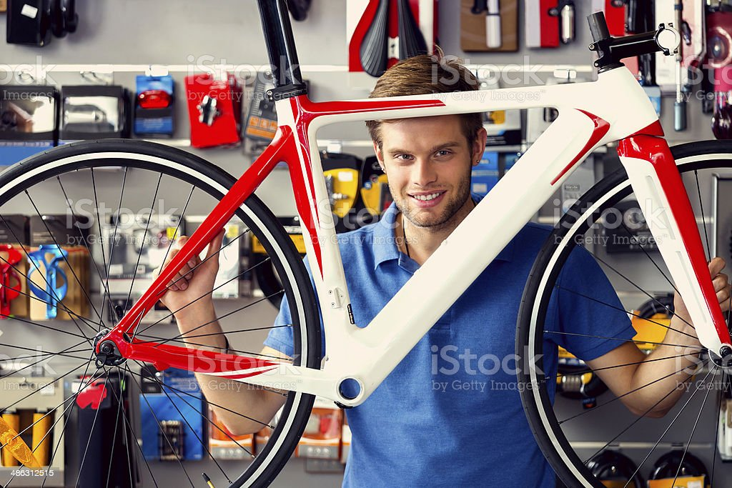 Man buying bicycle Man buying a bicycle in bike store, talking with shop assistant. Adult Stock Photo