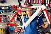 Man buying a bicycle in bike store, talking with shop assistant.