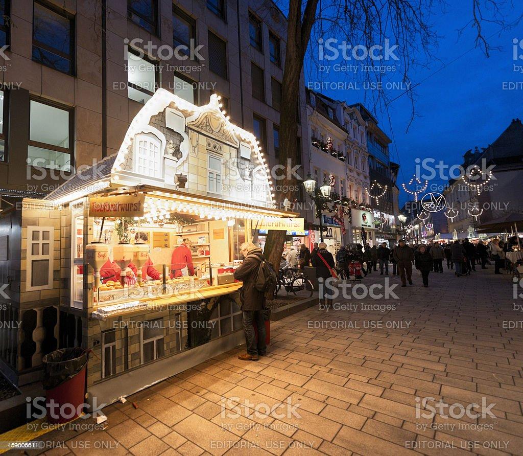 man buying bratwurst at Christmas Market in Dusseldorf Germany stock photo
