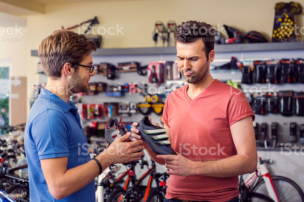 Man buying cycling shoes Man buying a cycling shoes in bike store, talking with shop assistant. Adult Stock Photo