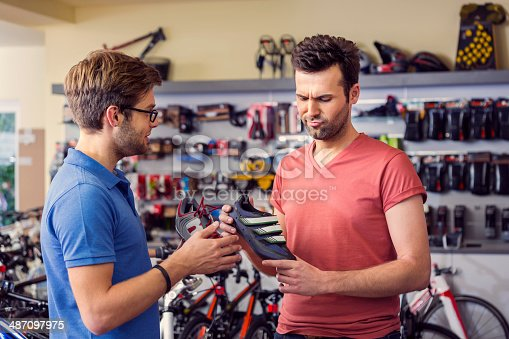 istock Man buying cycling shoes 487097975
