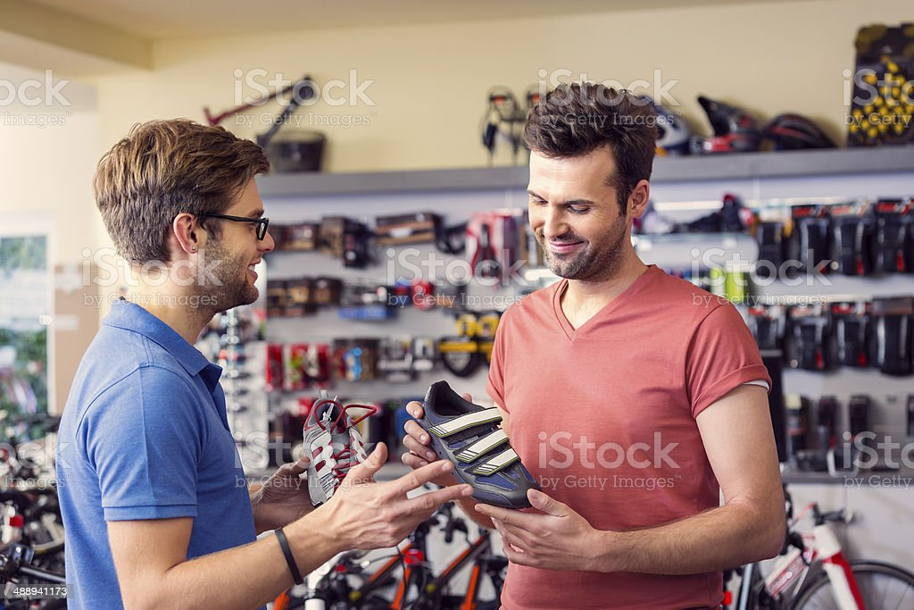 Man buying cycling shoes Man watching a cycling shoes in bike store, talking with shop assistant. Adult Stock Photo