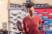 Man buying a cycling shoes in sport store, holding two different shoes in hand and making a decision.