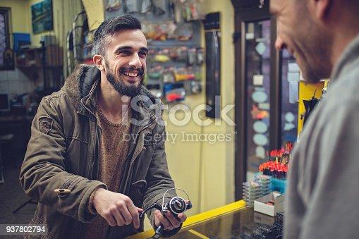 istock Man buying fishing equipment 937802794