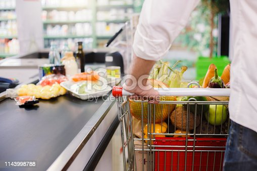 Person buying food products in the supermarket queue
