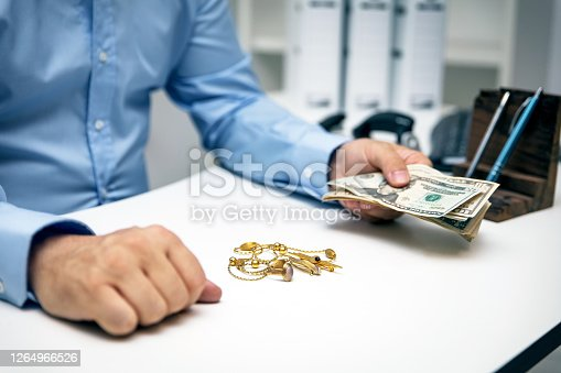 Man buying gold jewellry, pawn shop and us dollar banknotes