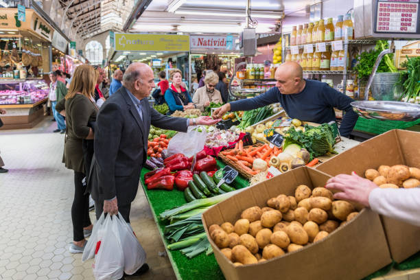 Man buying groceries at a merchants place in the Central Market in Valencia Spain Valencia, Spain - March 28, 2018: Man receives change after buying groceries at a merchants place in the Mercado Central (Central Market) in Valencia, Spain. The market hall was completed in 1928 and is one of the largest indoor fresh food markets in Europe. market hall stock pictures, royalty-free photos & images