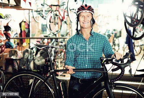 cheerful man buying new racing bicycle and helmet in sport shop