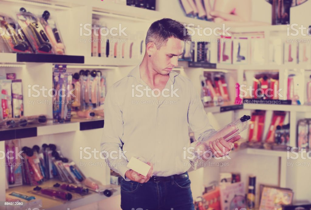 Man buying sex toys in shop stock photo