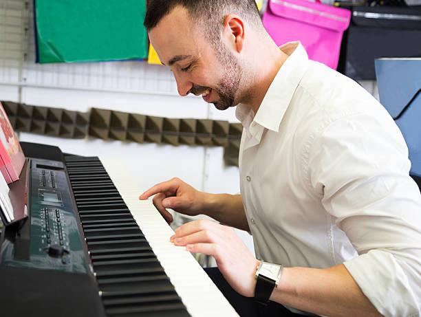 man buying synthesizer - klavier verkaufen stock-fotos und bilder
