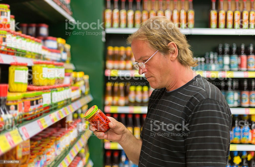 man buys hot peppers in the supermarket royalty-free stock photo
