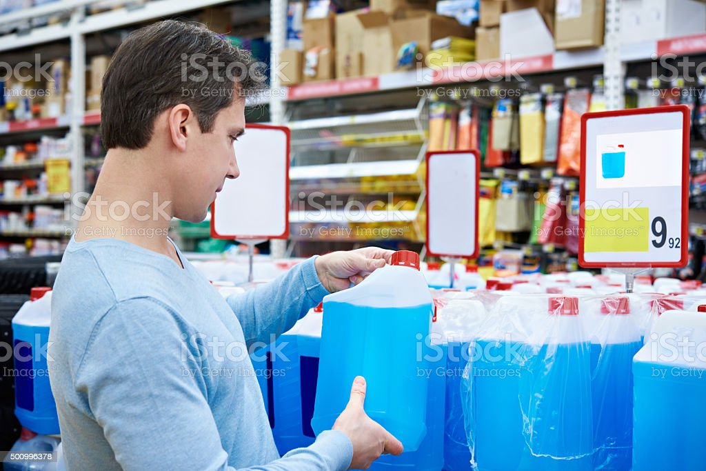 Man buys nonfreezing liquid in supermarket stock photo