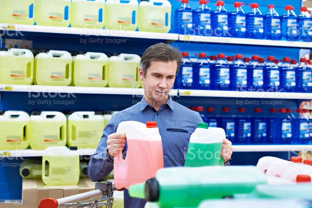 Man buys windshield washer fluid in shop stock photo