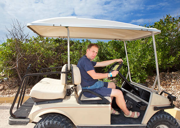 Man by golf car on the seashore. Mexico.