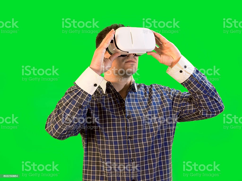 Man by Green Screen Holds Virtual Reality Headset to Eyes stock photo