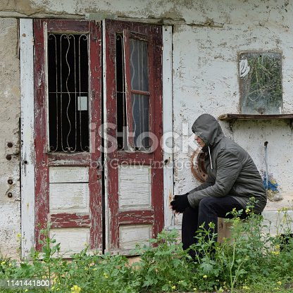 Man sitting on sink at the porch of an abandoned house with old door frame window and smudged mirror.