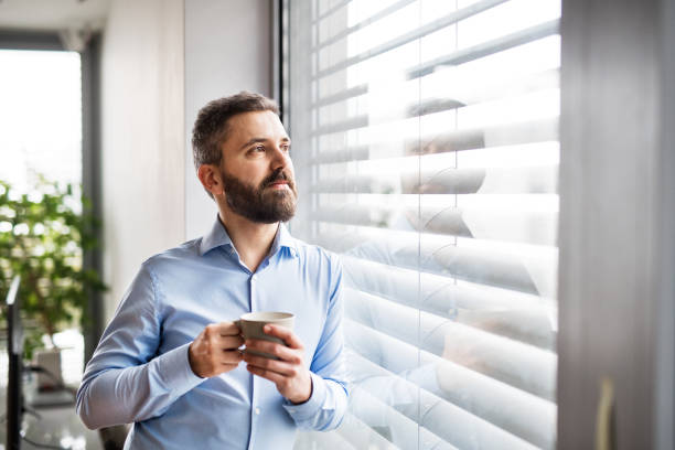 a man by the window holding a cup of coffee. smart home. - blinds stock pictures, royalty-free photos & images