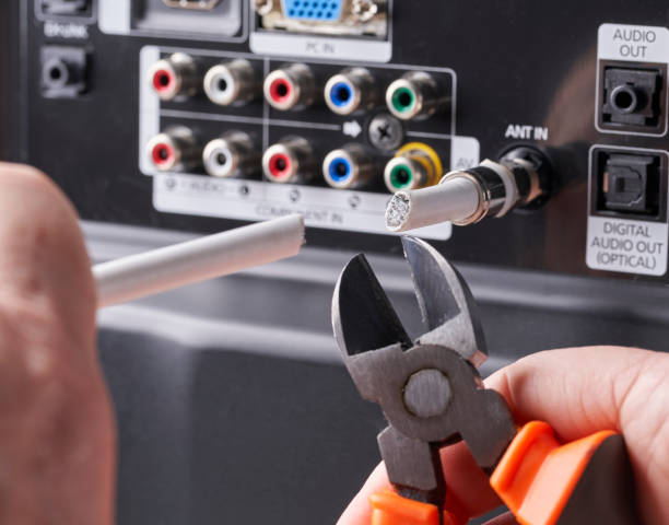 Man Cable cutting: cutting coaxial cable on back of television Cable cutting: cutting coaxial cable on back of television cable tv stock pictures, royalty-free photos & images