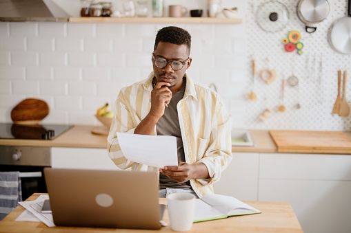 African man working from home, using laptop, paying utility bills. Young man doing taxes at home.
