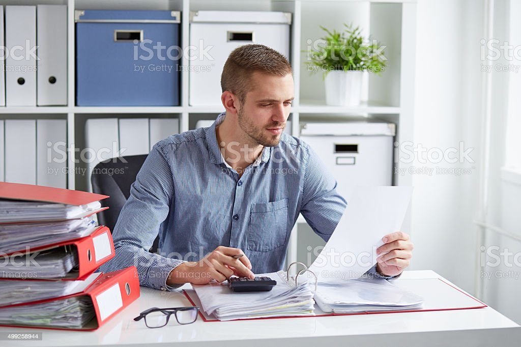 Man calculates taxes in office stock photo