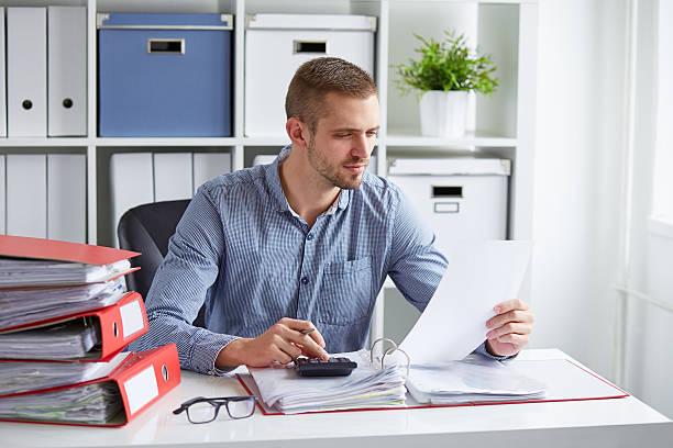 hombre calcula los impuestos en la oficina - gerente de cuentas fotografías e imágenes de stock