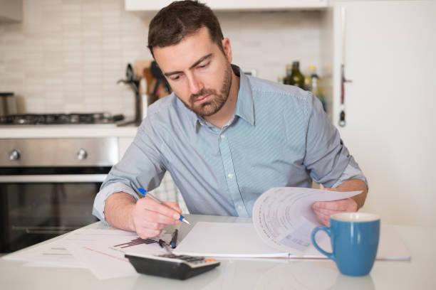 Homme, calcul des factures et des charges fiscales - Photo