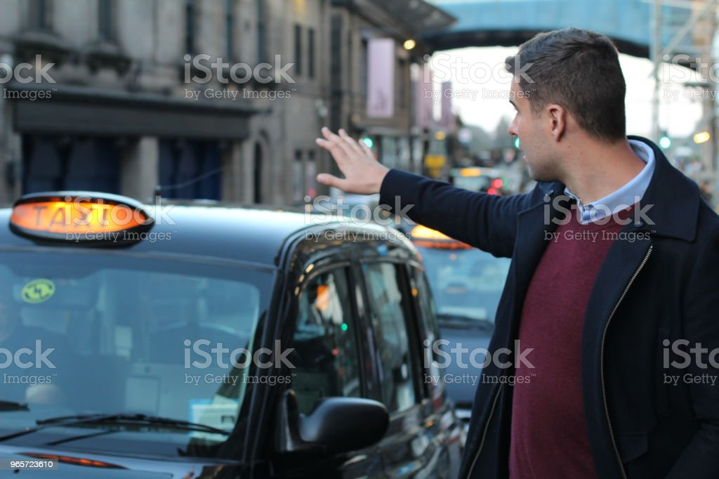 Man calling a traditional British cab - Royalty-free Achievement Stock Photo