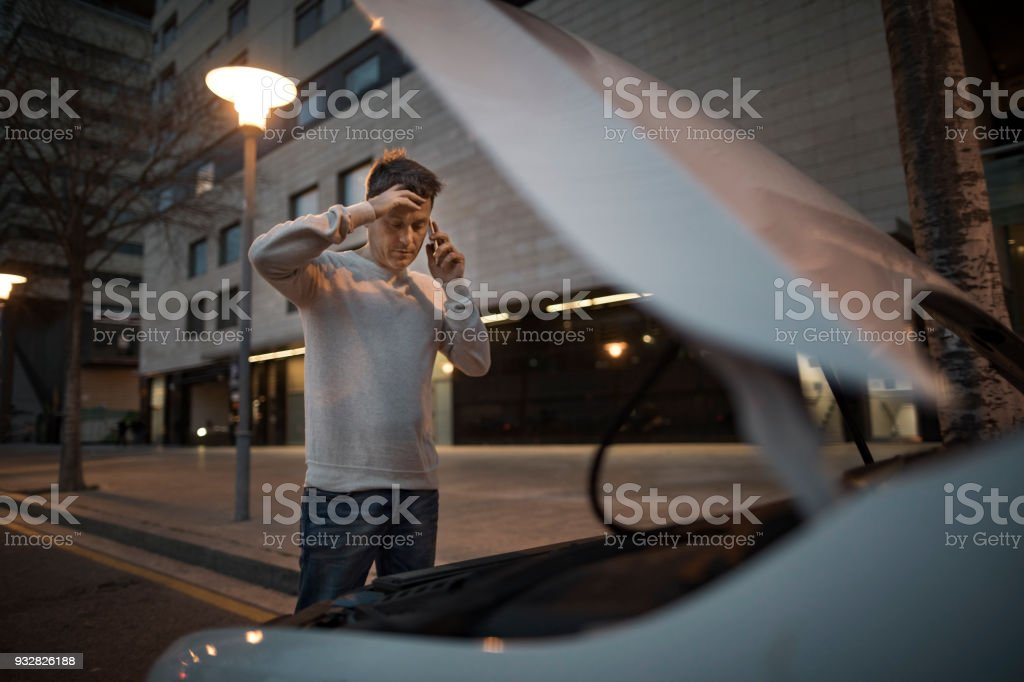 Man calling assistance after car breakdown stock photo