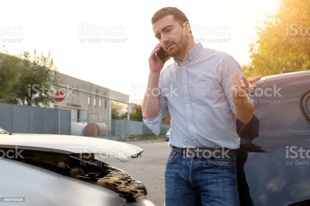 Man calling car mechanic insurance assistance after car accident stock photo