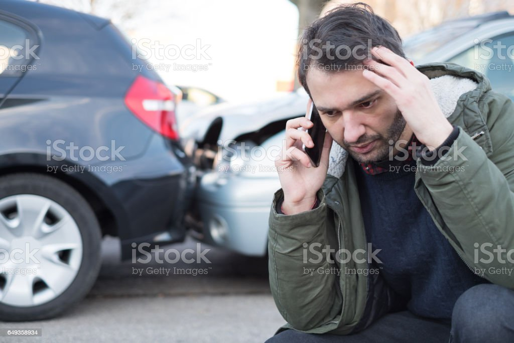 Man calling first aid after car crash stock photo
