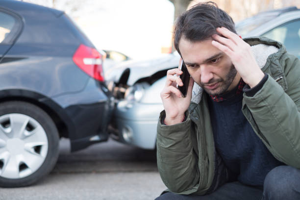 man calling first aid after car crash - car accident stock photos and pictures
