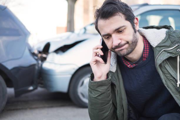 mannen ringer första hjälpen efter bilolycka - krockad bil bildbanksfoton och bilder