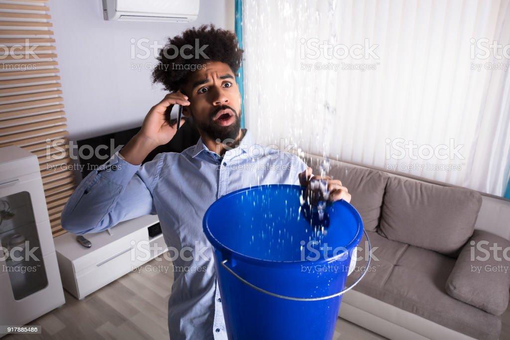 Man Calling Plumber While Leakage Water Falling Into Bucket stock photo