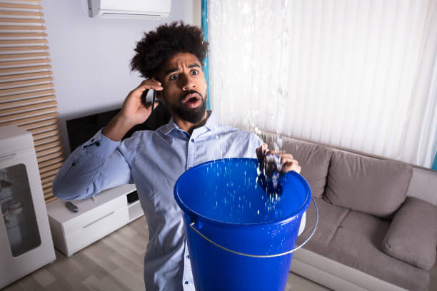 Man Calling Plumber While Leakage Water Falling Into Bucket stock photo